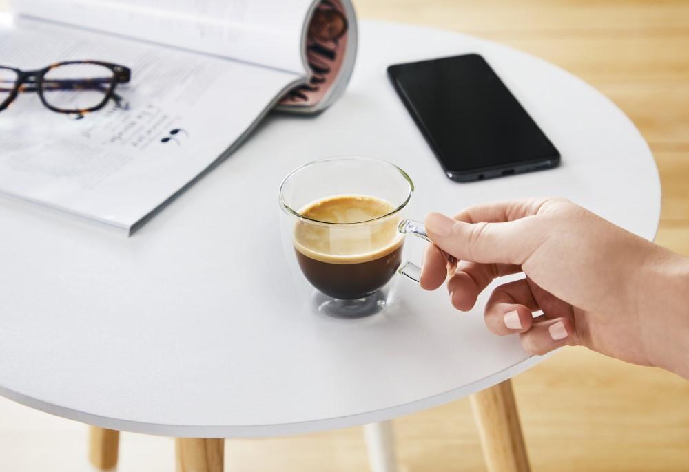 ceasca de cafea pe masa langa telefon