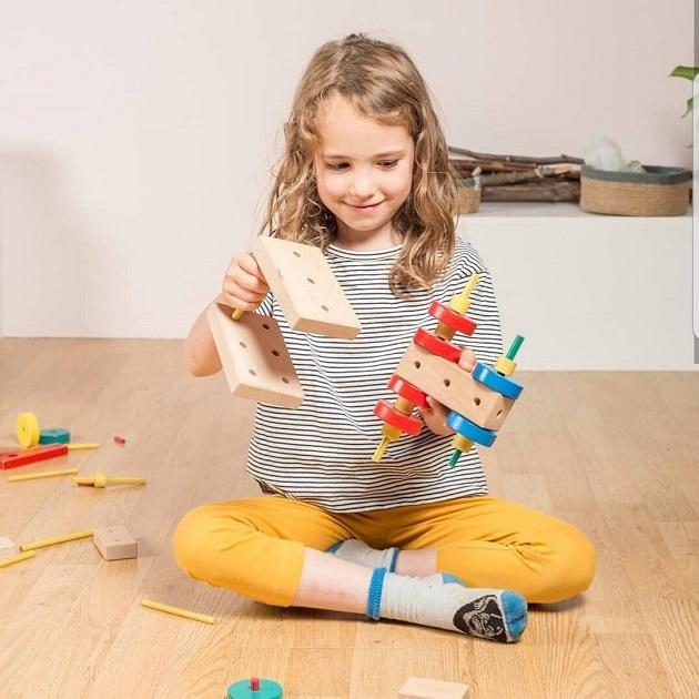 copil care se joaca cu jucarii din lemn