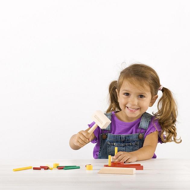Fetita care se joaca bucuroasa cu jucarii din lemn