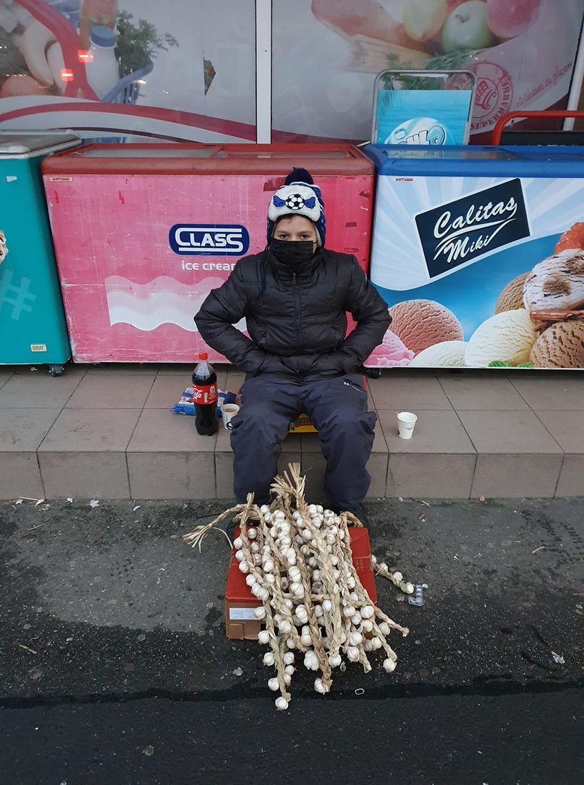 copil care vinde usturoi din arges