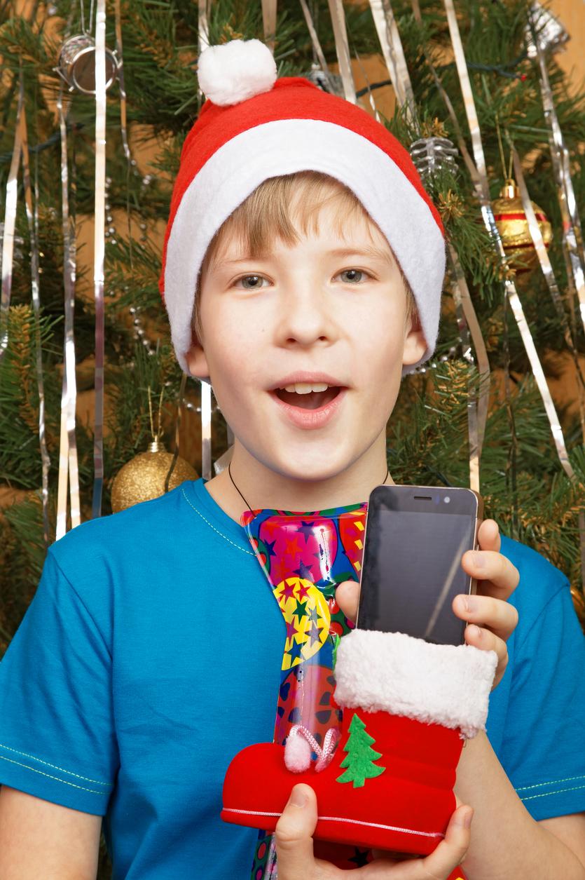 baiat care tine in mana un telefon cadou in fata bradului de Craciun cu o caciula rosie in cap