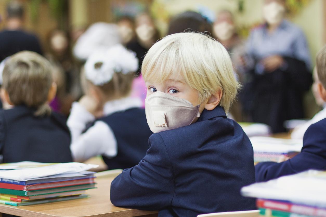 copil blond in banca la scoala purtand masca