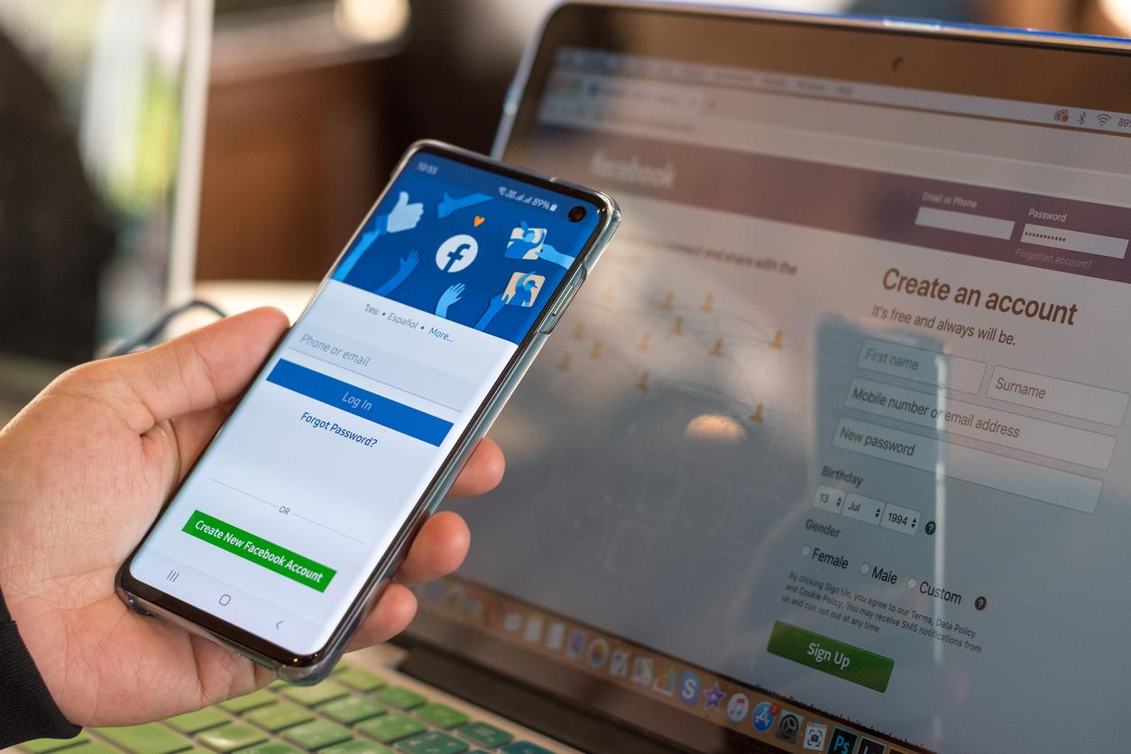 imagine cu o mana care  tine un telefon in mana si un latop pe fundal deschise pe facebook