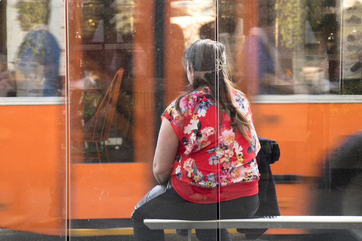 femeie obeza care asteapta autobuzul in statie