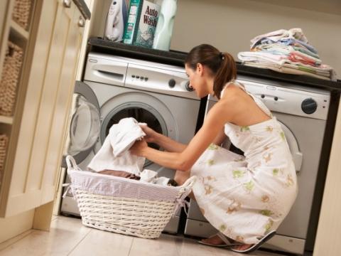 Tanara pune rufele in masina de spalat