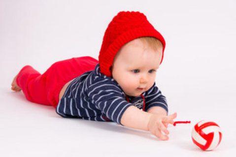 bebelus incercand sa atinga mingea