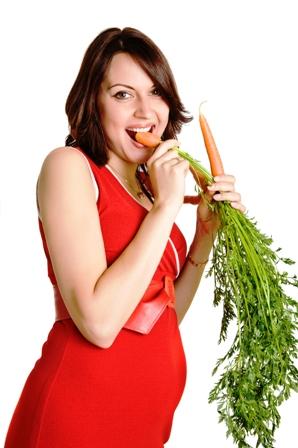 Poza femeie insarcinata mananc un morcov