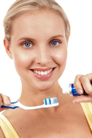 Poza femeie fericita cu ochii albastri se spala pe dinti