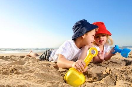 Poza copii la mare se joaca in nisip, cu galetusa