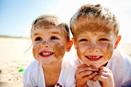 Poza copii fericiti se joaca la mare in nisip