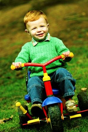 Poza baietel fericit pe bicicleta