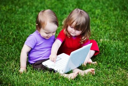 poza copilasi se joaca la laptop