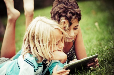 poza copii citesc in iarba de pe tableta