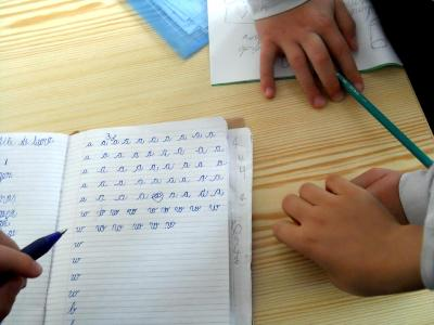 poza manute copii pe caietul de scris litere