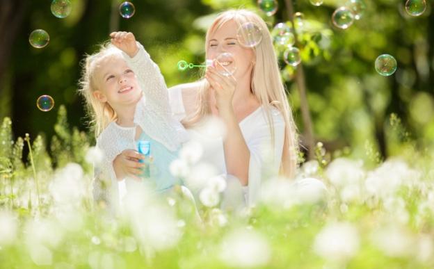 poza mama si copilul se joaca afara cu baloane de sapun
