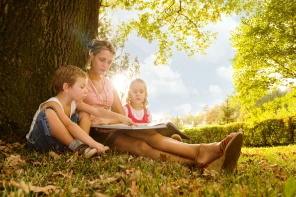 poza mama si copiii citesc povesti in natura