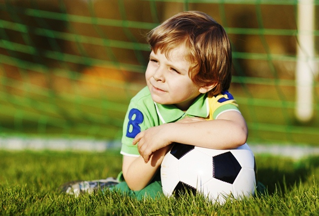 poza copil cu mingea pe terenul de fotbal