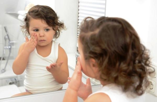 poza fetita se uita in oglinda