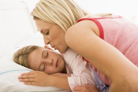 mama care isi saruta fetita de noapte buna