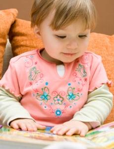 copil care se uita intr-o carte cu poze colorate