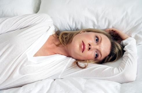Femeie in alb, intinsa pe pat