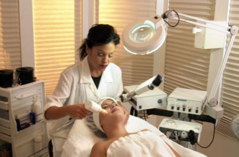 Medic dermatolog aplica tratament unei femei tinere