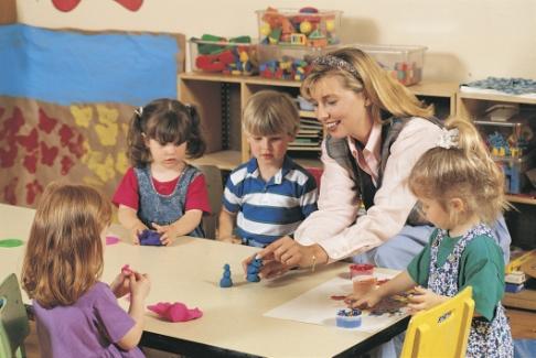 Educatoare si copii modeleaza plastilina