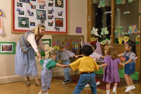 Educatoare si copii dansand