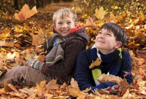 Copii jucandu-se cu frunze uscate