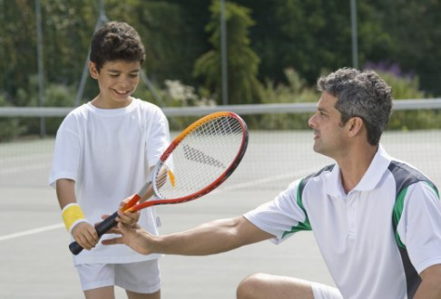 Baiat invata sa joace tenis