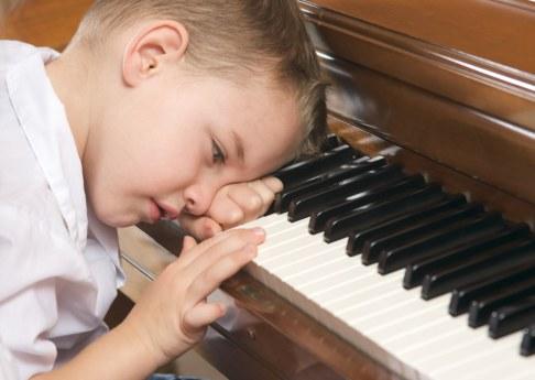 Copil obosit cantand la pian