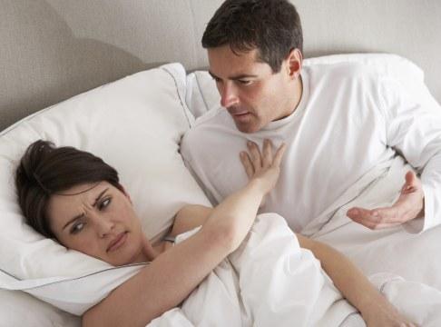 Femeie respingandu-si partenerul in pat