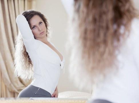 Femeie privindu-se in oglinda