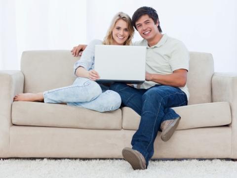 Cuplu stand pe canapea cu laptop in brate